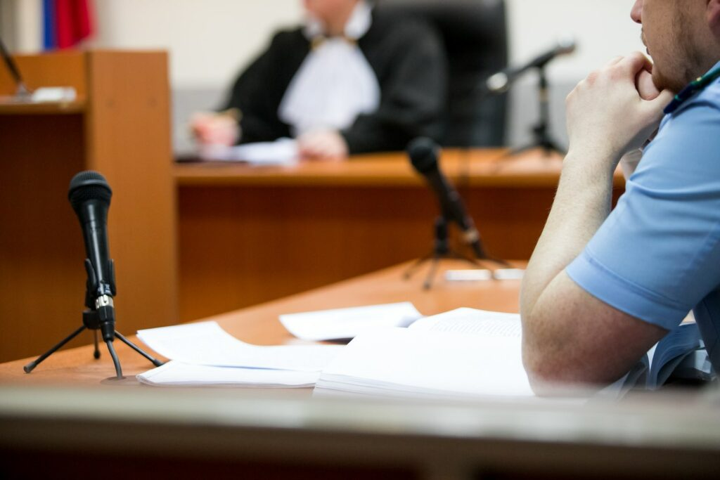 man on the stand behind microphone at a trial